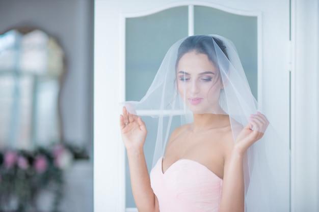Impresionante novia en vestido rosa se encuentra en la habitación