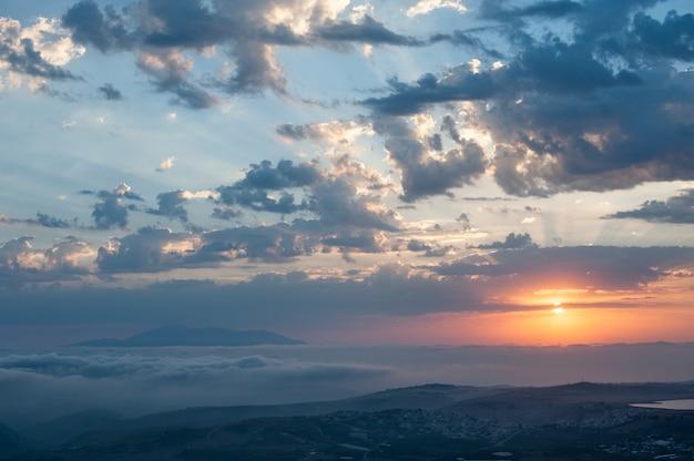 Impresionante paisaje con amanecer y nubes.