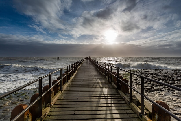Impresionante paisaje de un amanecer sobre el muelle del océano en westkapelle, zelanda, países bajos