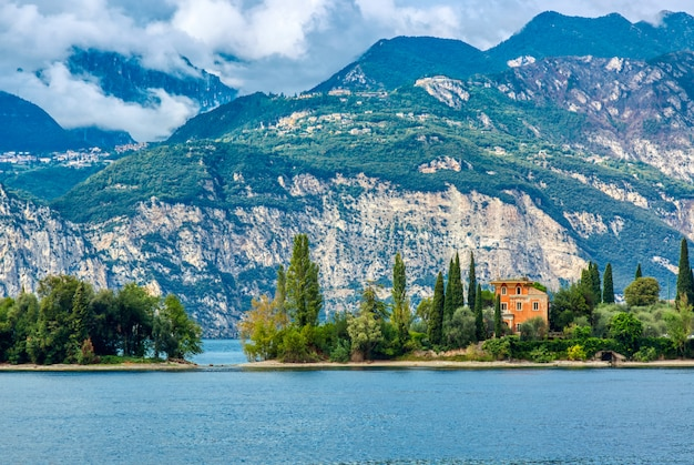 Impresionante paisaje del lago de garda con casita, tres y montaña.