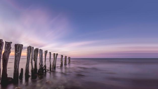 Impresionante paisaje de palos de madera en medio del océano bajo el cielo colorido