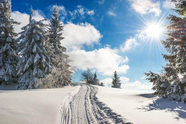 Impresionante y pintoresco paisaje de caminos trillados de invierno en una colina cubierta de nieve cubierto