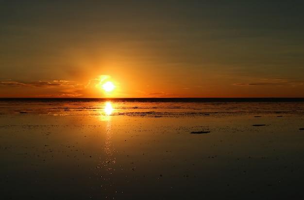 Impresionante puesta de sol reflejada en el salar de uyuni inundado de bolivia, américa del sur