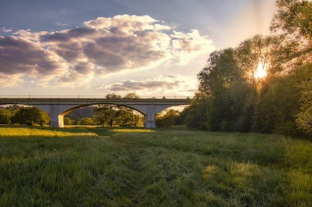 Impresionante puesta de sol sobre un bosque verde con un largo puente en el medio