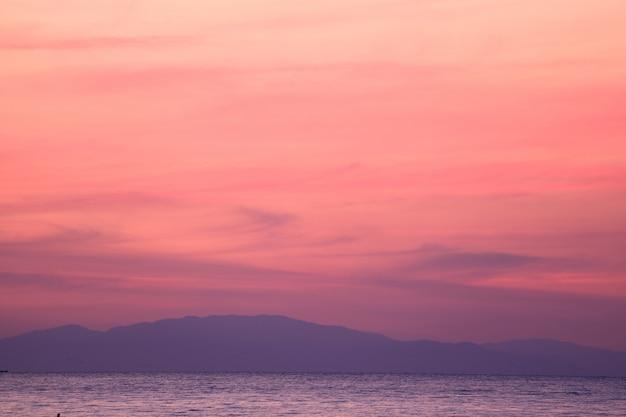 Impresionante rosa pastel y el cielo púrpura de la salida del sol sobre el golfo de tailandia con la cordillera en el fondo