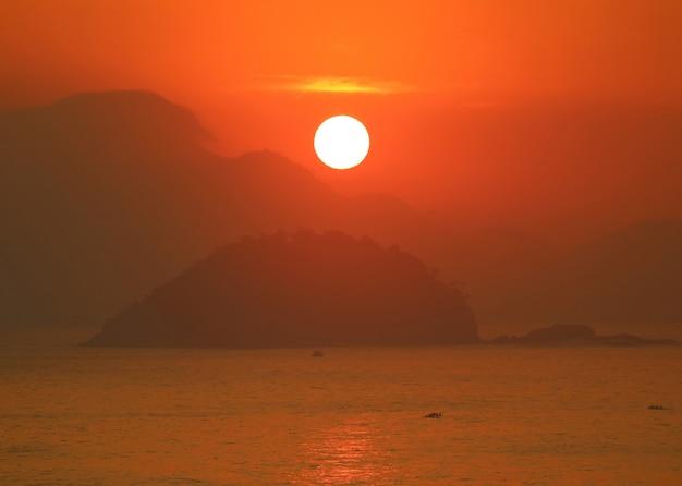 Impresionante salida del sol sobre la vista del océano atlántico desde la playa de copacabana, río de janeiro, brasil