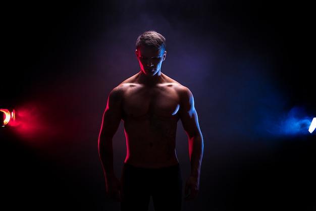 Impresionante silueta culturista. culturista atlético guapo guapo. cuerpo musculoso fitness en escena de humo de color oscuro. hombre perfecto tatuaje, posando.