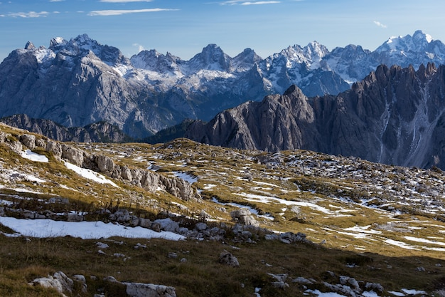 Impresionante tiro de rocas nevadas en los alpes italianos bajo el cielo brillante