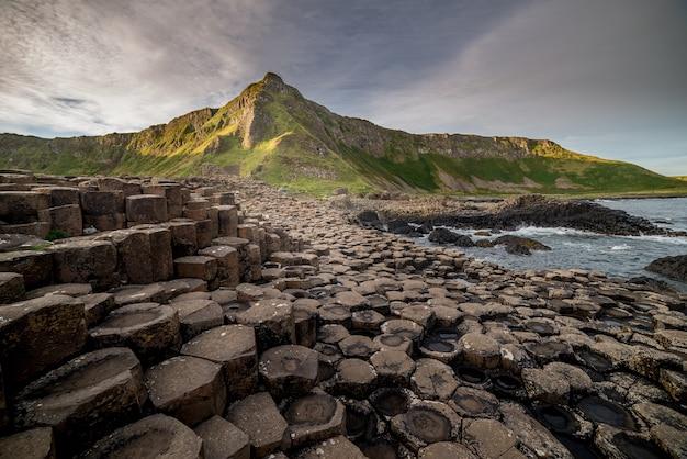 Impresionante vista de la curiosa unión columnar hexagonal junto al mar cerca de la base de una montaña
