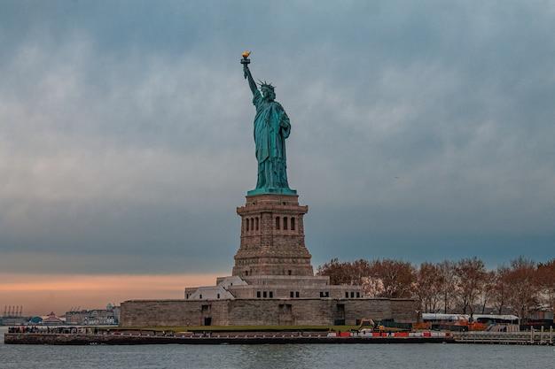 Impresionante vista de la estatua de la libertad contra el oscuro cielo nublado