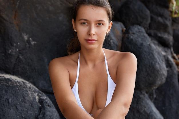 Impresionante vista de la hermosa mujer caucásica con pecho perfecto, viste bikini blanco