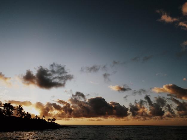 Impresionante vista de las hermosas nubes en el cielo sobre el océano tranquilo junto a la playa