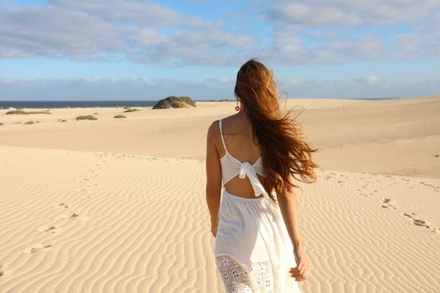 Impresionante vista de joven caminando descalzo sobre las dunas del desierto al atardecer en corralejo, fuerteventura