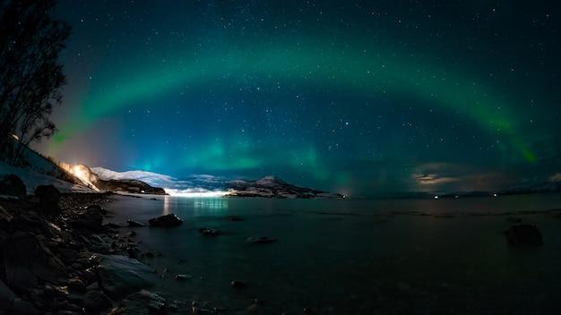 Impresionante vista del lago y las montañas bajo el cielo fascinante con una aurora