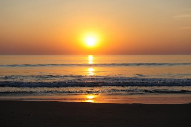 Impresionante vista del mar en los rayos del sol poniente, la luz del sol rojizo se refleja en el agua.