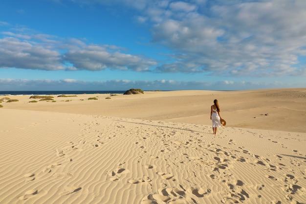 Impresionante vista de mujer caminando en la playa de corralejo dunas, fuerteventura, islas canarias