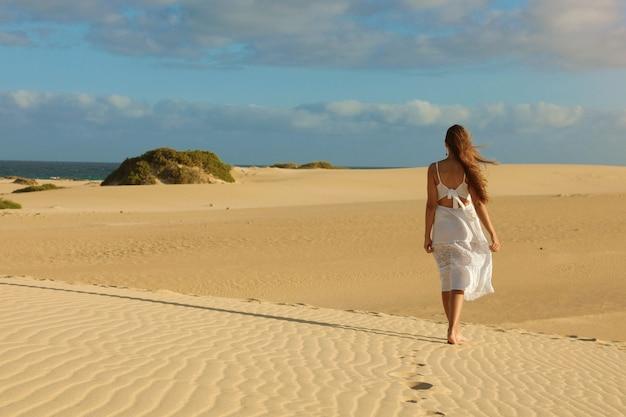 Impresionante vista de mujer joven caminando descalzo sobre las dunas del desierto al atardecer en corralejo, fuerteventura