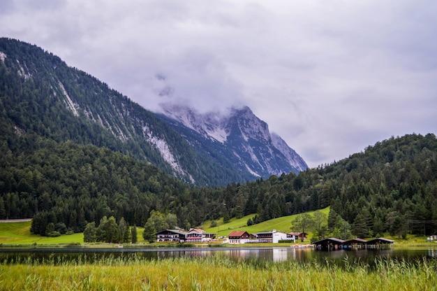 Impresionante vista del río entre los árboles verdes y la montaña cubierta de nieve bajo un cielo nublado