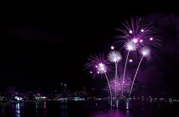 Impresionantes fuegos artificiales de color púrpura vivo salpicando en el cielo nocturno sobre el puerto