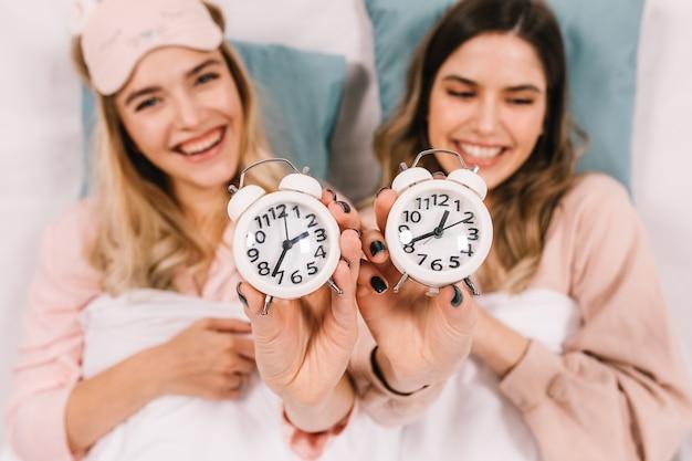 Impresionantes mujeres en pijama sonriendo en la cama