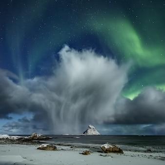 Impresionantes nubes sobre el océano y la playa cubierta de nieve debajo de las auroras en el cielo