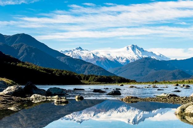 Impresionantes paisajes del reflejo de la montaña de nieve en el río. cielo azul y algo nublado.
