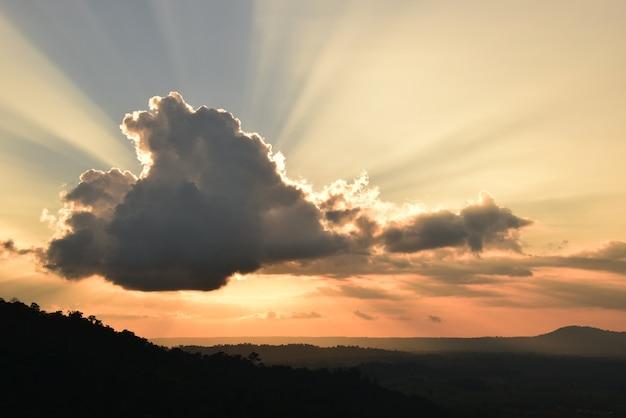 Los impresionantes rayos del sol de las nubes en el cielo al atardecer.