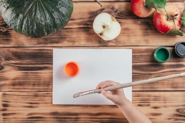 Impresiones de calabaza y manzana tutorial paso a paso para niños de halloween. paso 4: la mano del niño sostiene el pincel. vista superior