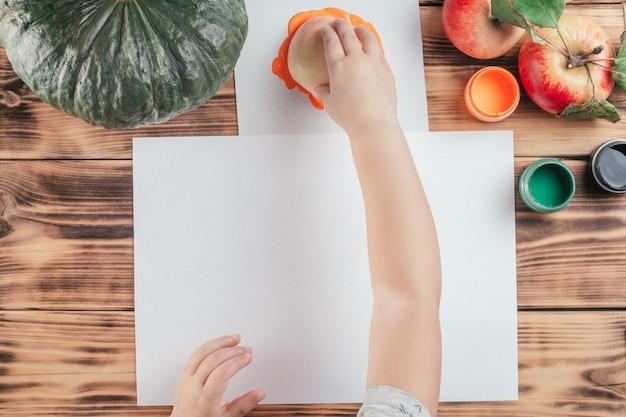Impresiones de calabaza y manzana tutorial paso a paso para niños de halloween. paso 6: la mano del niño sumerge la mitad de la manzana en pintura gouache naranja sobre papel. vista superior