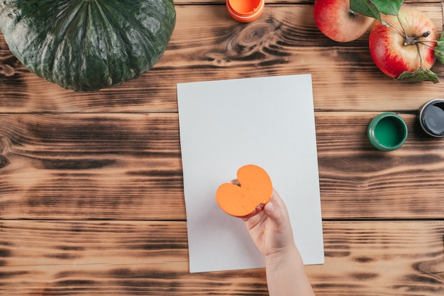 Impresiones de calabaza y manzana tutorial paso a paso para niños de halloween. paso 7: la mano del niño sostiene la mitad de la manzana pintada en gouache naranja para hacer la impresión. vista superior