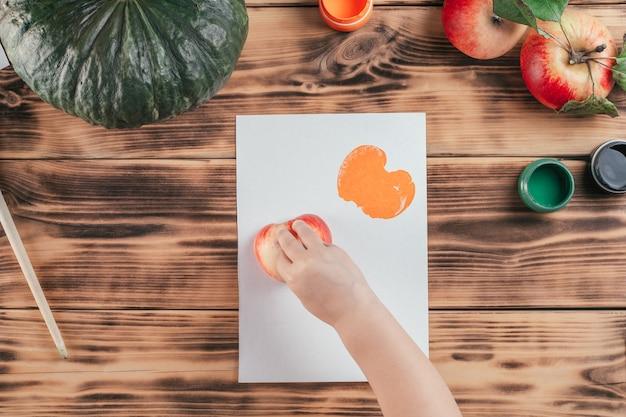Impresiones de calabaza y manzana tutorial paso a paso para niños de halloween. paso 8: la mano del niño deja huellas en papel con la mitad de la manzana pintada con pintura gouache naranja. vista superior