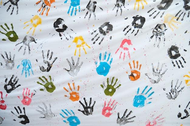 Impresiones coloridas de la mano en la tela blanca