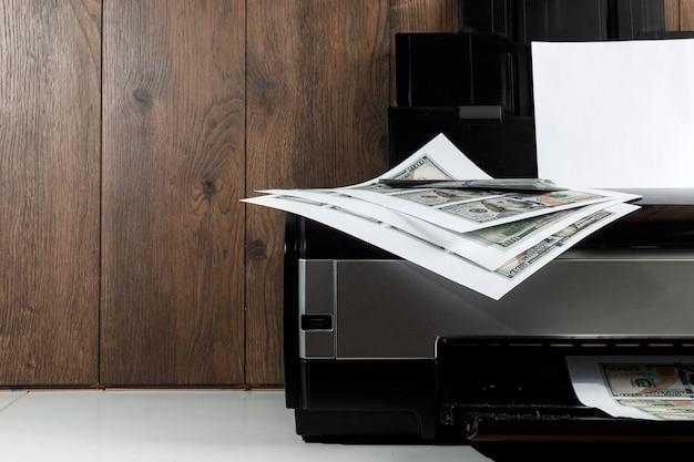 Impresora y dólares estadounidenses impresos