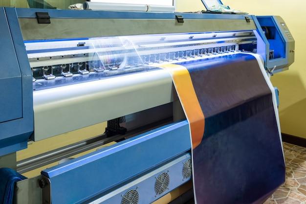Impresora de inyección de tinta grande con cabezal trabajando en vinilo azul