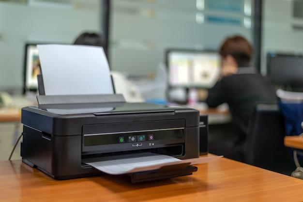 Impresora negra en la oficina con enfoque suave y luz en el fondo.