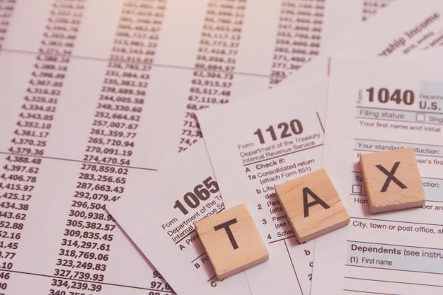 Impuesto con bloques de madera del alfabeto, pluma sobre fondo de formulario de impuesto de estados unidos