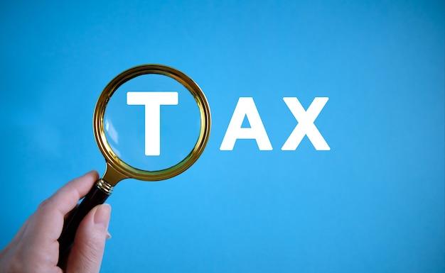 Impuesto - texto con una lupa sobre un fondo azul