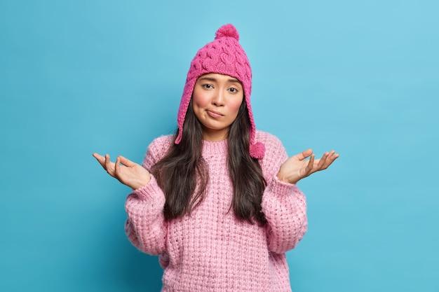 Incierta hermosa mujer asiática tiene el cabello oscuro, palmas de las manos hacia los lados se encuentra despistado y confundido vestido con un sombrero de suéter de invierno se ve con expresión cuestionada aislada sobre la pared azul del estudio