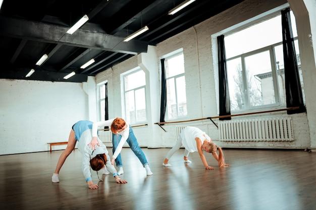 Inclinación profunda. dos lindas chicas de pelo largo de la generación z haciendo ejercicio en el estudio mientras practican la inclinación profunda