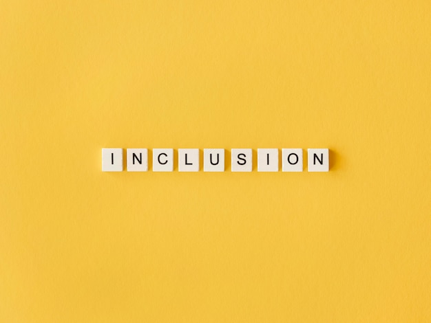 Inclusión palabra escrita en letras de scrabble sobre fondo amarillo