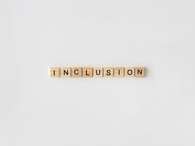 Inclusión palabra escrita en letras de scrabble sobre fondo blanco.