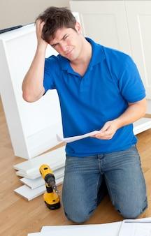Incomprehensive caucasian man leyendo las instrucciones para armar muebles en la cocina