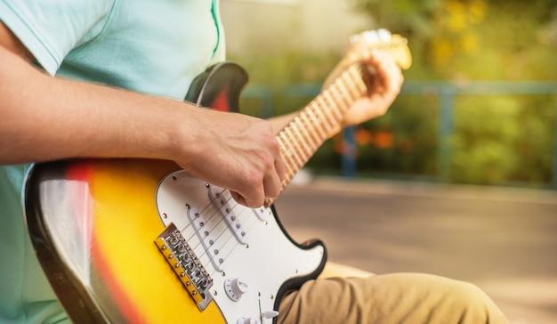 Inconformista feliz del hombre joven que se sienta tocando la guitarra, cierre para arriba, luz del sol del verano, al aire libre
