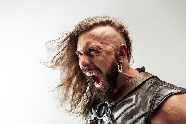Incontrolable. cabello largo rubio y modelo masculino musculoso en traje de vikingo de cuero con el gran martillo cosplay aislado sobre fondo blanco de estudio. guerrero de fantasía, antiguo concepto de batalla.