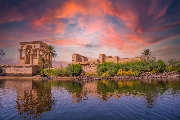 Increíble amanecer anaranjado en el templo de philae, una construcción grecorromana vista desde el río nilo, un templo dedicado a isis, diosa del amor. asuán. egipcio