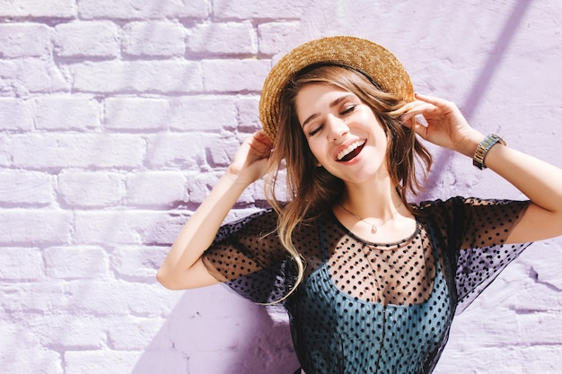 Increíble chica de pelo largo con ropa elegante disfrutando de un buen día fuera de pie con los ojos cerrados bajo el sol