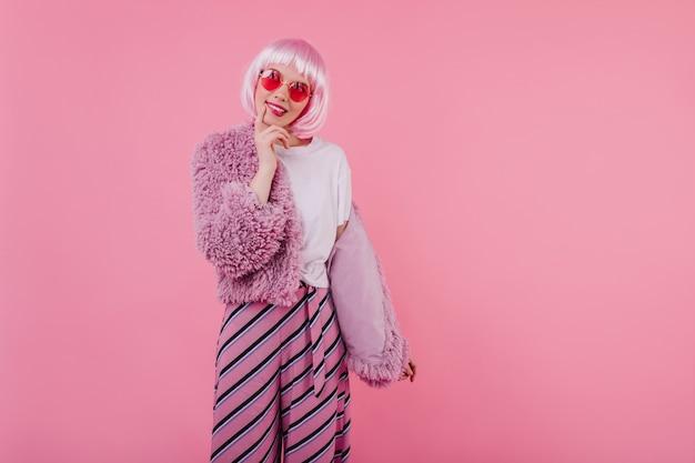 Increíble chica en peruke pensando en algo durante la sesión de fotos. foto interior de atractiva mujer joven con pelo corto de color rosa