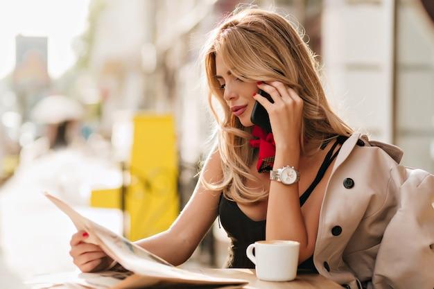 Increíble chica rubia discutiendo noticias con un amigo mientras habla por teléfono