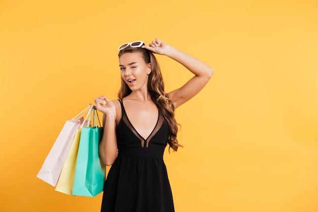 Increíble dama en vestido negro guiñando un ojo y sosteniendo bolsas de la compra.