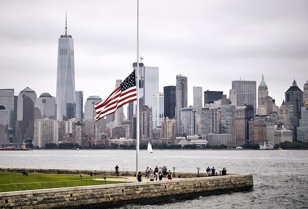 Increíble foto de la bandera estadounidense en un parque en el fondo del horizonte de manhattan